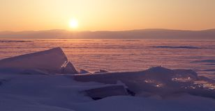 Transparent ice floe on a hummock field on the frozen Siberian Lake Baikal at sunset in winter. Transparent ice floe on a hummock field on the frozen Siberian royalty free stock images