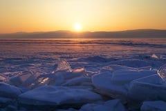 Transparent ice floe on a hummock field on the frozen Siberian Lake Baikal at sunset in winter. Transparent ice floe on a hummock field on the frozen Siberian stock image
