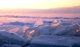 Transparent ice floe on a hummock field on the frozen Siberian Lake Baikal at sunset in winter. Royalty Free Stock Images