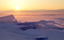 Transparent ice floe on a hummock field on the frozen Siberian Lake Baikal at sunset in winter. stock photo