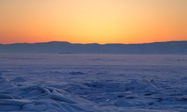 Transparent ice floe on a hummock field on the frozen Siberian Lake Baikal at sunset in winter. Transparent ice floe on a hummock field on the frozen Siberian royalty free stock image