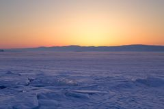 Transparent ice floe on a hummock field on the frozen Siberian Lake Baikal at sunset in winter. Transparent ice floe on a hummock field on the frozen Siberian stock photo