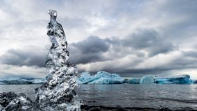 Transparent ice on glacial shore on cloudy day stock image