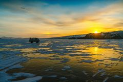 Pattern on ice of lake Baikal during sunset with car. Siberia Russia stock photography