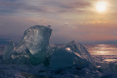 Transparent ice on sunset sky background. Royalty Free Stock Photo
