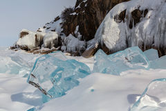 Transparent icicles in the snow on a background of icy rocks. Royalty Free Stock Images