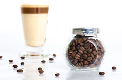Transparent jar with coffee beans and latte macchiato  o Stock Photos