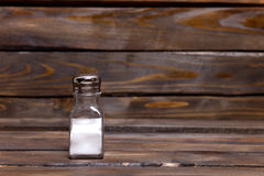 Transparent jar of shaker with salt on wooden background Stock Photography