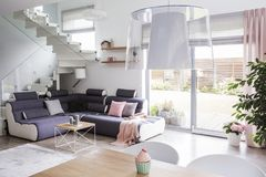 Transparent light shade above a wooden dining table in a white l. Iving room interior with a modern corner sofa and stairs with glass barricade royalty free stock photo