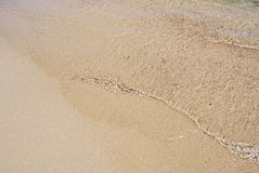 Transparent and light waves on the golden seashore. As background Royalty Free Stock Photos