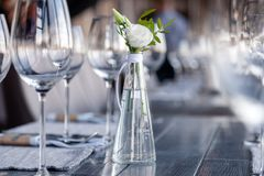 Transparent modern setting, glass vase with bouquet flowers on table in restaurant. Wine and water glasses stand on wooden table. Restaurant interior, serving stock photo