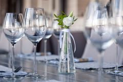 Transparent modern setting, glass vase with bouquet flowers on table in restaurant. Wine and water glasses stand on wooden table. Restaurant interior, serving royalty free stock images