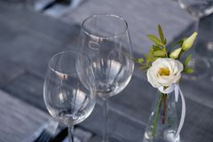 Transparent modern setting, glass vase with bouquet flowers on table in restaurant. Wine and water glasses stand on wooden table. Restaurant interior, serving royalty free stock photography
