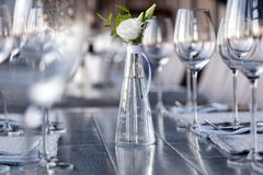 Transparent modern setting, glass vase with bouquet flowers on table in restaurant. Wine and water glasses stand on wooden table. Restaurant interior, serving stock photos