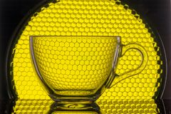 Transparent mug on a background of yellow honeycomb for photography. Transparent mug on a background of yellow honeycomb stock image