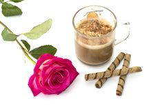 The transparent mug of a cappuccino decorated with a flower and cookies, a still life Royalty Free Stock Photo