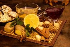 Tea with Lemon in a transparent mug near teapot a raspberry jam, mint ginger glass and cinnamo brewery and chocolate cookies on a. Transparent mug with Lemon Tea Stock Photo