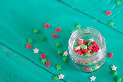 Transparent open glass jar with colorful confectionery powder in. Transparent open glass jar with colorful Christmas sprinkles in form of stars on green Royalty Free Stock Photo