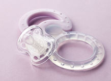Transparent pacifier on pink background Stock Photo