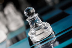 Transparent Pawn On Blue Chessboard With Crooked Angle Stock Photo