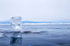 A transparent piece of ice on the surface of the blue frozen lake Baikal Royalty Free Stock Images