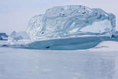 A transparent piece of ice on surface of blue frozen lake Baikal Royalty Free Stock Image