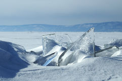 Transparent pieces of ice on the surface of the iced nad snowcaped pond. Baikal lake. Stock Image
