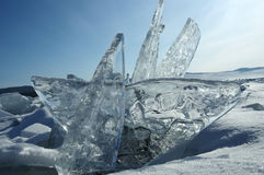 Transparent pieces of ice on the surface of the iced nad snowcaped pond. Baikal lake. Royalty Free Stock Photos