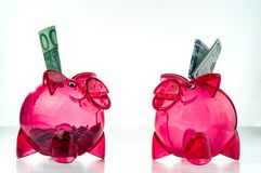 Transparent piggy banks with dollar and euro banknotes. Diversification of investments royalty free stock images