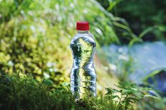Transparent plastic A bottle of clean water with a red lid stands in the grass and moss on the background of a rugged. Mountain river. The concept of pure Stock Photo