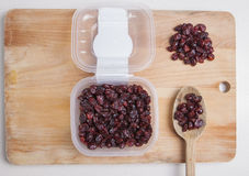 Transparent plastic bowl full of dried blueberry with wooden spo Stock Photo