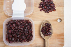 Transparent plastic bowl full of dried blueberry with wooden spo Stock Photos
