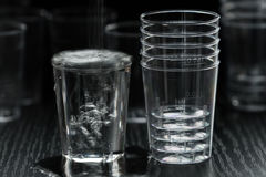 Transparent plastic cup. The disposable clear plastic cups to 40 ml with graduation to receive small portions of beverages, water and other liquids. Close-up on stock images