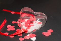 Transparent plastic heart with red ribbon and red and white hearts around. Transparent plastic heart with red ribbon and some red and white hearts in and around Stock Photography