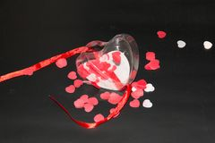 Transparent plastic heart surrounded of some red and white hearts. Transparent plastic heart with red ribbon and some red and white hearts in and around it on a Stock Image