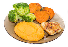 Transparent plate with fresh green broccoli, smashed sweet potatoes and slice of orange sweet potatoes, chiken meat Royalty Free Stock Images