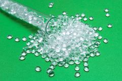 Transparent Polyethylene granules on a green background.The concept of free bpa. HDPE Plastic pellets. Plastic Raw material . ID. PE stock photo