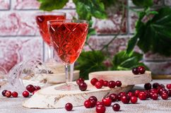 Transparent red drink. With cranberries on a wooden background. Selective focus royalty free stock photography