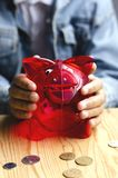 A transparent red piggy bank pig in the children`s hands of a girl stock photography