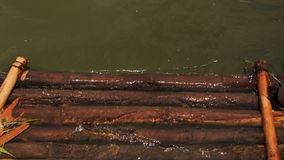 Transparent river water washes out wooden logs of bank platform stock video footage