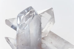 Transparent rock crystals on white. Cluster of several transparent quartz crystals close-up on a white background Royalty Free Stock Image