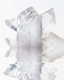Transparent rock crystals on white reflected in a water. Cluster of several transparent quartz crystals close-up on a white background reflected in a water Royalty Free Stock Photography
