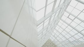 Transparent roof and sky. Glass panels and sunlight. Building of new business center.  stock video footage