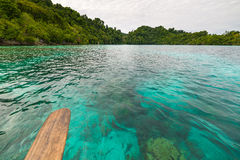 Transparent sea, dramatic sky, traditional culture and green forest in the remote Malenge Beach, Togean Islands, Sulawesi, Indones Stock Photos