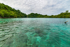 Transparent sea, dramatic sky, traditional culture and green forest in the remote Malenge Beach, Togean Islands, Sulawesi, Indones Royalty Free Stock Images