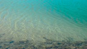 Transparent sea water and crystal clear water with stones on sandy bottom. Turquoise water and calm sea waves on exotic. Beach stock footage