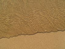Transparent sea wave on the sand Stock Photos