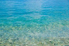 Transparent shallow water with rocky bottom, fading away to deeper area at top.Crystal clear water with transparent. Transparent shallow water with rocky bottom Royalty Free Stock Image