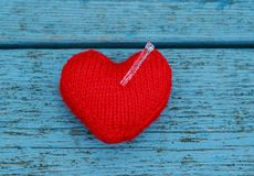 Transparent sharp cold icicle impaled warm knitted heart on blue. Wooden table Royalty Free Stock Images