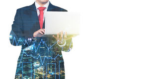 A transparent silhouette of a man in formal suit who is looking for some data in the laptop. Panorama of evening New York city and financial charts on the Stock Photography